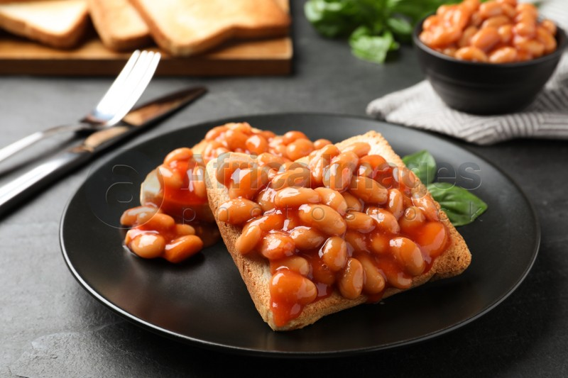 Toasts with delicious canned beans on black table