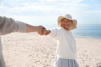 Mature couple spending time together on sea beach, closeup