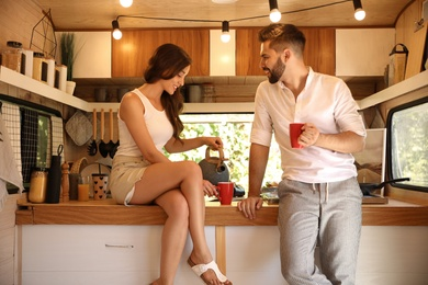 Happy young couple with cups in trailer. Camping vacation