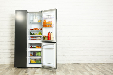 Open refrigerator filled with food near white brick wall, space for text