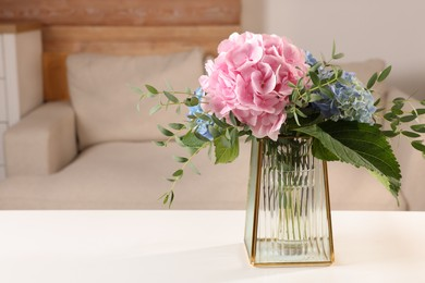 Beautiful hortensia flowers in vase on white table indoors. Space for text