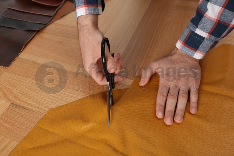 Man cutting orange leather with scissors at wooden table, closeup