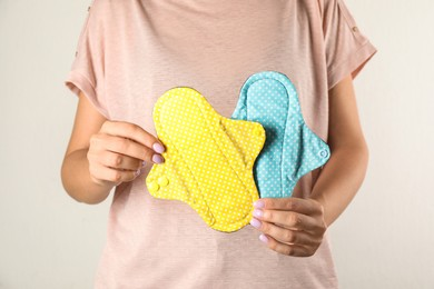 Woman holding reusable cloth menstrual pads isolated on white, closeup