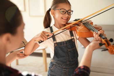 Young woman teaching little girl to play violin indoors