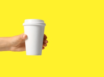 Woman holding takeaway paper coffee cup on yellow background, closeup. Space for text