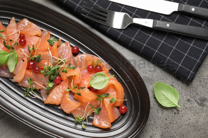 Delicious salmon carpaccio served on grey table, flat lay