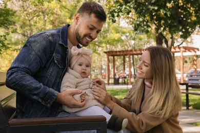 Happy parents with their baby in park on sunny day