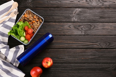 Flat lay composition with thermos and lunch box on black wooden background, space for text