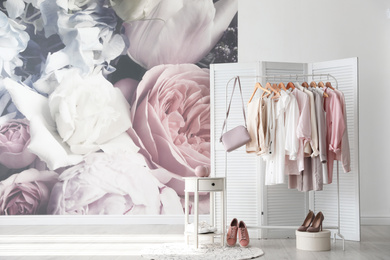 Rack with stylish women's clothes and handbag indoors. Interior design