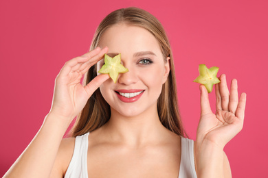Young woman with cut carambola on pink background. Vitamin rich food