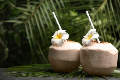Young peeled coconut with straws, palm leaf and flowers on black table. Space for text