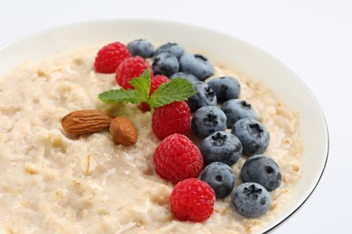 Tasty oatmeal porridge with raspberries, blueberries and almond nuts in bowl on white background, closeup