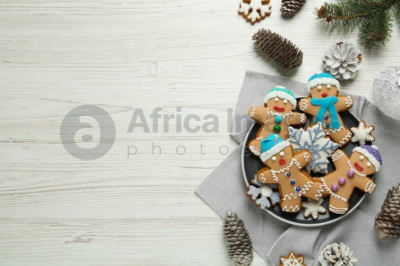 Delicious Christmas cookies, pine cones and fir branches on white wooden table, flat lay. Space for text