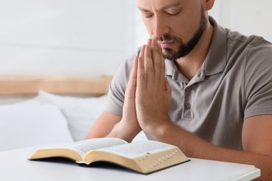 Religious man with Bible praying in bedroom, closeup