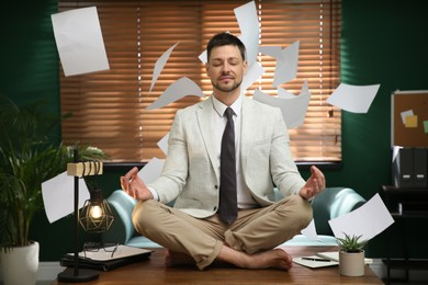 Calm businessman meditating on office desk in middle of busy work day