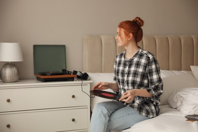Young woman using turntable in bedroom at home