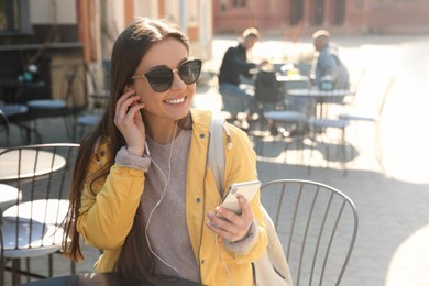 Happy young woman with earphones and mobile phone listening to music in outdoor cafe