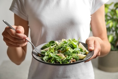 Woman with tasty pear salad on blurred background, closeup