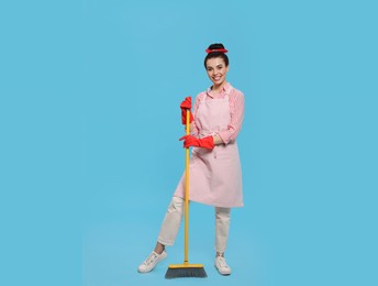 Young housewife with broom on light blue background, space for text