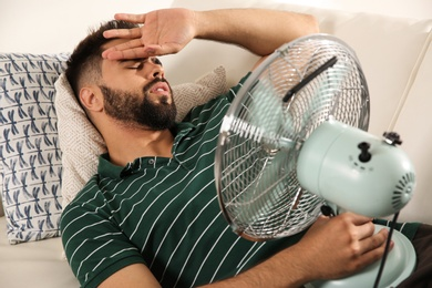 Man with fan suffering from heat at home. Summer season