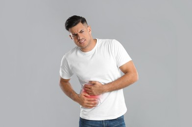 Man suffering from liver pain on grey background