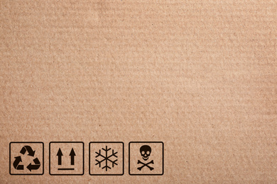 Cardboard box with packaging symbols as background, closeup