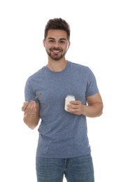 Happy young man with yogurt and spoon on white background