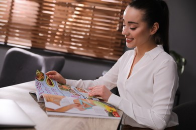 Happy woman reading magazine at workplace in office