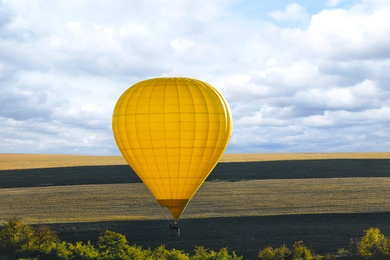 Colorful hot air balloon flying over field