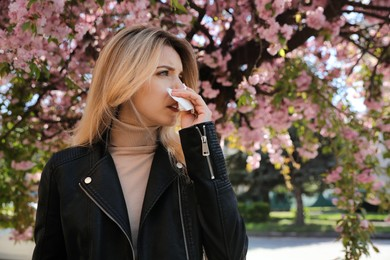 Woman suffering from seasonal pollen allergy near blossoming tree outdoors