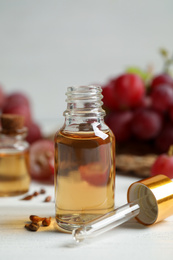 Bottle of natural grape seed oil on white wooden table. Organic cosmetic