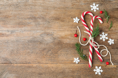 Flat lay composition with candy canes on wooden background, space for text. Winter holidays