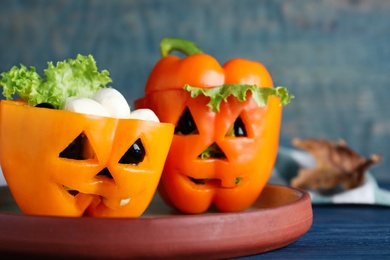 Bell peppers with black olives and lettuce as Halloween monsters on blue wooden table, closeup