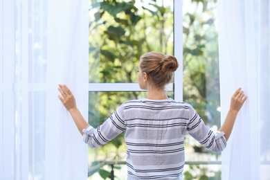 Young woman opening curtains and looking out of window at home