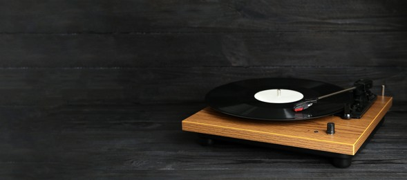 Turntable with vinyl record on black wooden background. Space for text