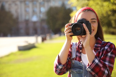 Young photographer taking picture with professional camera outdoors. Space for text