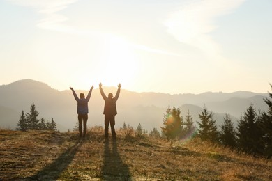 Couple enjoying sunrise in mountains, back view. Space for text