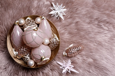 Christmas baubles on pink faux fur, flat lay