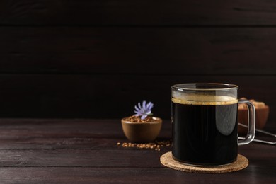 Glass cup of delicious chicory drink on wooden table, space for text