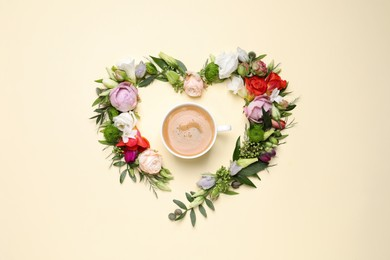 Beautiful heart made of different flowers and coffee  on beige background, flat lay