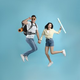 Couple of tourists jumping on light blue background