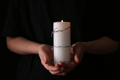 Woman holding candle with barbed wire on black background, closeup. Holocaust memory day