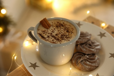 Tasty hot drink and chocolate cookies surrounded by Christmas lights, closeup