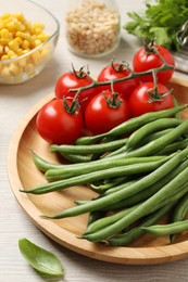 Fresh green beans and other ingredients for salad on white wooden table, closeup