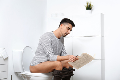 Man with newspaper sitting on toilet bowl in bathroom