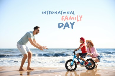 Happy parents teaching son to ride bicycle on sandy beach near sea. Happy Family Day