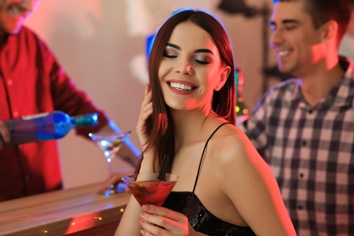 Beautiful young woman with glass of martini cocktail in bar