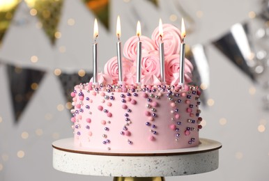 Beautifully decorated birthday cake on stand against blurred festive lights