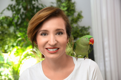 Happy woman with Alexandrine parakeet on blurred background