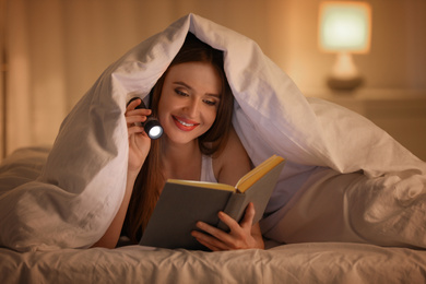 Young woman with flashlight reading book under blanket in bedroom